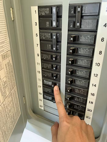 This picture shows an electrician doing a panel upgrade in Berkeley and Oakland. Circuit breaker is being tested after installed.